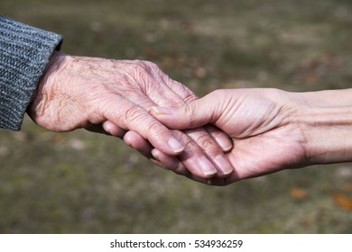Close-up of elderly caregiver and daughter's hands