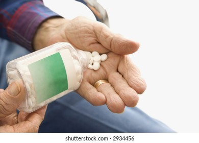 Close-up of elderly male Caucasio pouring pills into hand.
