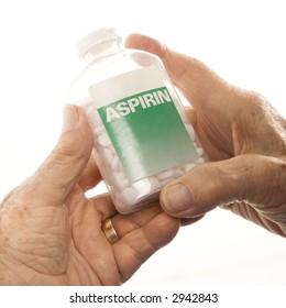 Close-up of elderly male Caucasion hands holding aspirin bottle.