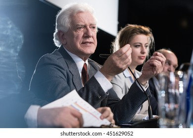 Close-up of an elderly man explaining something at a press conference
