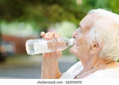Closeup of elderly woman drinking water