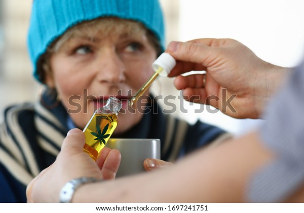 Close-up of elderly woman receives sedative drops from doctor. Glass bottle with leaf sign. Prescription herbal meds. Traditional medicine cannabinoid oil and healthcare concept