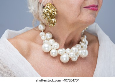 Close-up of elderly woman wearing beautiful elegant expensive jewelry