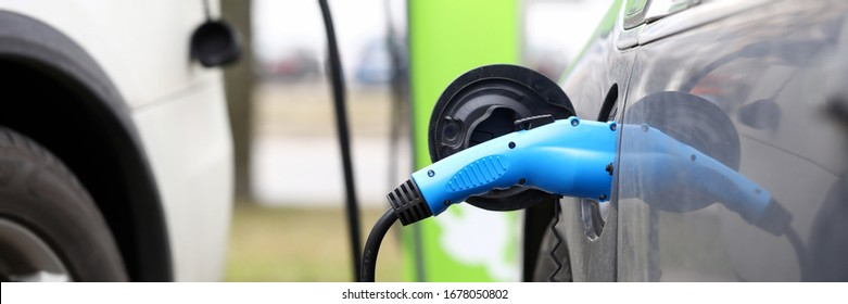 Close-up of electric car public charging station on city street. Power supply for electrocar. Refueling for e-mobility. Innovation and modern vehicle concept