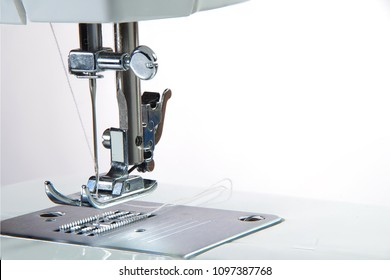 Closeup of the electric household sewing machine and item of clothing.