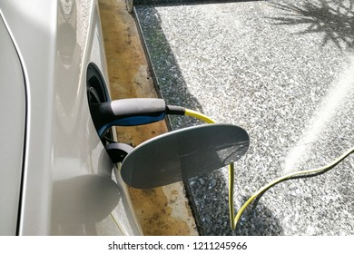 Closeup of electric hybrid car being charged with socket on wall