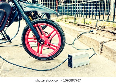 close-up of an electric motorcycle charging, e-bike, is charged with current and then inserted into the bike, green ecology,