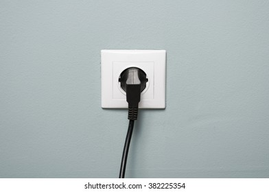 Closeup of electric socket with black cable plugged in as energy source concept