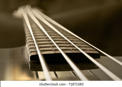 closeup of electrical bass guitar fingerboard, sepia