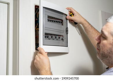 A closeup of an electrical engineer working in a power electrical panel in apartment building. Check the parameters of the power plant.