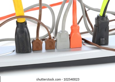 Closeup of an electrical power strip with several different cords plugged in.