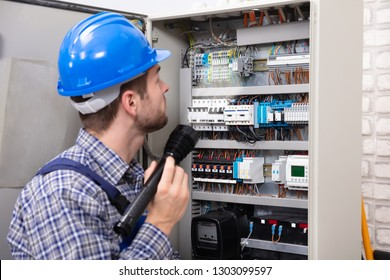 Close-up Of A Electrician Examining A Fuse Box With A Torch