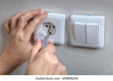 Closeup of electrician hands during electric wall socket and light switch repair using screwdriver.