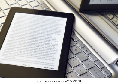 Closeup Of Electronic Book Reader With Blurred Text On Silver Laptop Keyboard  With Reflection From The Screen