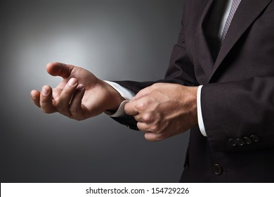 Close-up of elegance man hands with cufflink over dark background