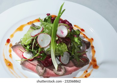 close-up elegant beautifully decorated salad tongue with vegetables and sauce on a white plate