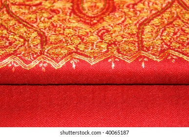 closeup of an elegant red pashmina shawl with delicate yellow embroidery