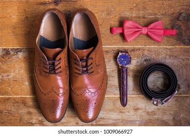 Closeup of elegant stylish brown male formal accessories isolated on brown wooden background. Top view of leather belt, shoes, watch and bowtie. Preparation for wedding or bussiness day concept.