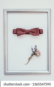 Closeup of elegant stylish brown male accessories isolated on white background in wooden frame. Top view of bow-tie, belt, floral corsage Preparation for wedding concept. Vertical color photo.