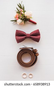 Closeup of elegant stylish brown male accessories isolated on white wooden background. Top view of bow-tie, belt, floral corsage, golden rings. Preparation for wedding concept. Vertical color photo.