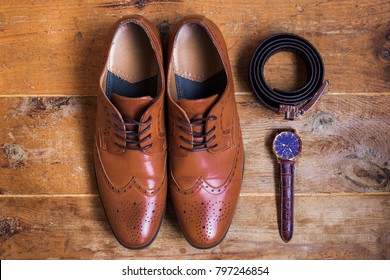 Closeup of elegant stylish brown male formal accessories isolated on brown wooden background. Top view of leather belt, shoes and watch. Preparation for wedding or bussiness day concept.