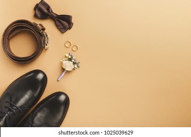 Closeup of elegant stylish male accessories isolated on beige background. Top view of bow-tie, belt, shoes, floral corsage, golden rings. Preparation for wedding concept, copy space