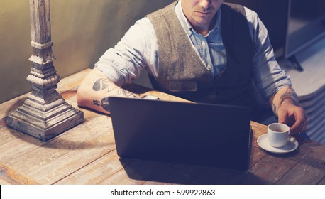 9b5c4c861 Closeup of elegant tattooed man working at home on laptop while sitting at  the wooden table