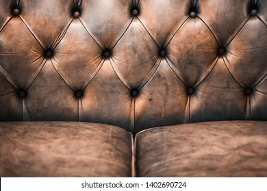 Close-up of an elegant vintage Chesterfield pattern brown leather sofa with seat and cushions