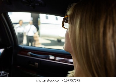 Closeup of elegant woman in limousine at airport terminal