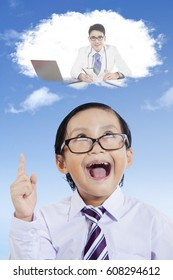 Closeup of elementary student is imagining his dream while looking at a cloud in the sky