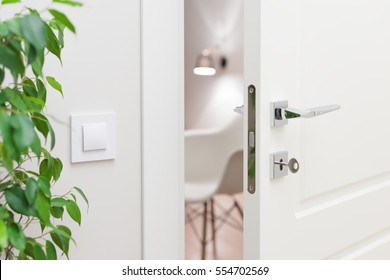 Close-up elements of the interior of the apartment. Ajar white door. Chrome door handle and lock with key. The light switch on the wall