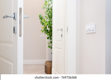 Close-up elements of the interior of the apartment. Ajar white door. Chrome door handle and lock. The light switch on the wall