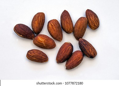 Closeup of Eleven Almonds scattered on a White Background