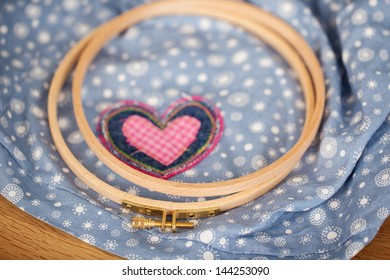 Closeup of embroidery hoops with heart on fabric in workshop