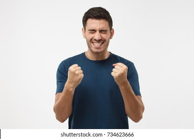 Closeup of emotional European man isolated on gray background showing white teeth while screaming with joy and victorious expression, holding hands in gesture of winner, looking extremely happy