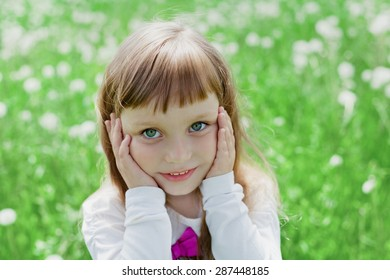 Closeup emotional portrait of cute little child girl or kid with beautiful soulful eyes standing on a green meadow