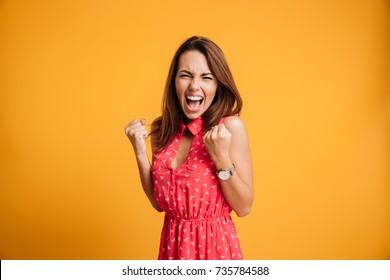 Close-up of emotional young attractive woman with keeping hands in fists, isolated on yellow background
