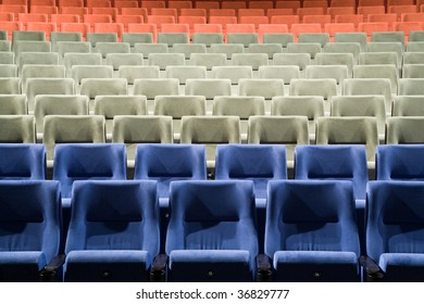 Close-up of empty cinema auditorium with lines of blue, green and red chairs.