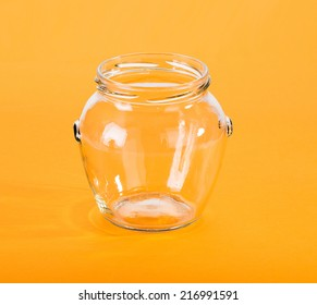 Closeup of empty glass jar on yellow background.