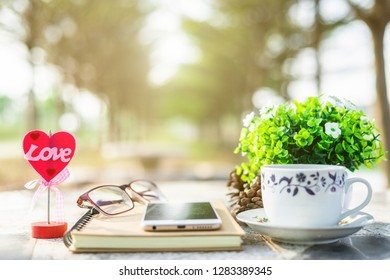 Close-up of empty notebook,smartphone,spectacles and cup of coffee on Marble floor background. Love concept with heart desktop,Valentine's Day.