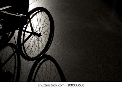 Closeup empty wheelchair on dark background and shadow
