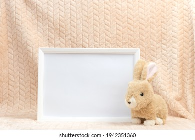 Close-up of empty white frame without picture. Cute childs toy near framework. Concept of childhood, play, studio decoration and friendly atmosphere, copyspace
