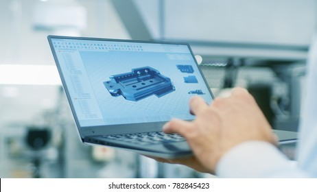 Close-up of the Engineer Holding Laptop with CAD Component Model on Screen. In the Background Modern Factory Equipment.