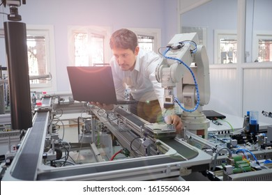 Close-up of Engineer holding product to teach robot arm position of program and checking on laptop for smart factory automation. Industry 4.0 concept; artificial intelligence in smart factory.