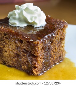 Closeup of english toffee pudding topped with vanilla whipped cream