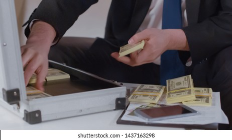 Closeup of entrepreneur counting money from briefcase, kickback in business