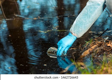 close-up environmentalist hand of a researcher, produces a process of taking a sample of water from a river