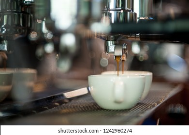 Close-up of espresso pouring from coffee machine , Fresh coffee prepared in the coffee machine. Espresso in two white cups.