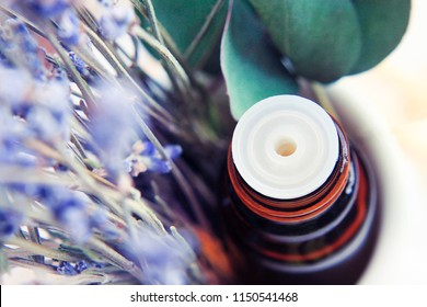 Closeup essential oil bottle with soft blurred lavender flowers, purple and green aroma leaves.