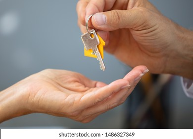 Close-up Of An Estate Agent's Hand Giving House Key To Woman